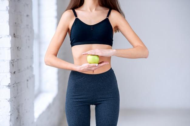 Bella donna esile in sportwear scuro che tiene mela verde nelle mani vicino alla sua pancia attraente