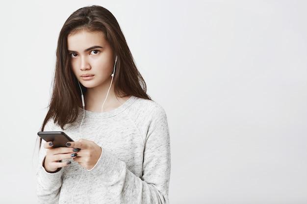 Bella donna europea carina con lunghi capelli castani, tenendo smartphone mentre si ascolta la musica in cuffia, esprimendo preoccupazione.