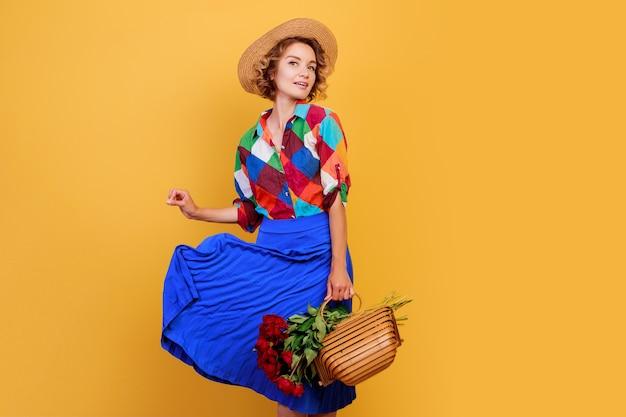 Bella donna europea in abito blu tenendo il mazzo di fiori su sfondo giallo. cappello di paglia. atmosfera estiva.