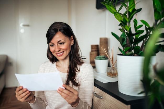 Bella donna felice casual guardando la lettera ricevuta.