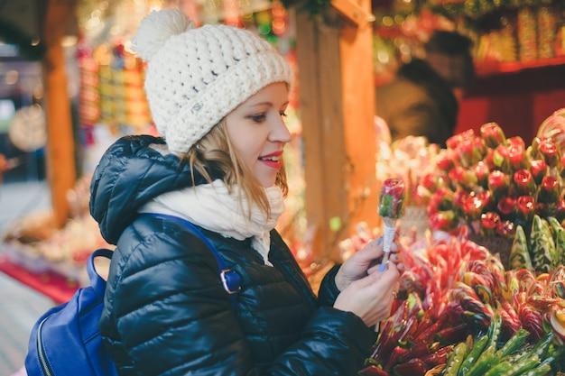 Bella donna felice che seleziona le caramelle tradizionali di festa