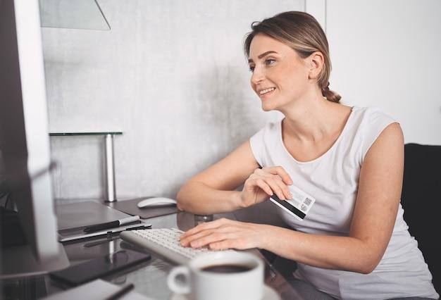Bella donna felice con carta di credito in mano e utilizzando la tastiera del computer portatile. lavoro imprenditrice o imprenditore. shopping online, e-commerce, internet banking, spendere soldi concetto