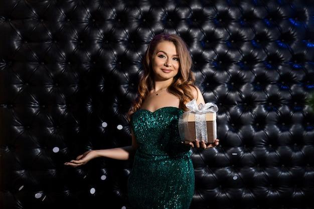 Bella donna felice con confezione regalo alla festa di celebrazione.