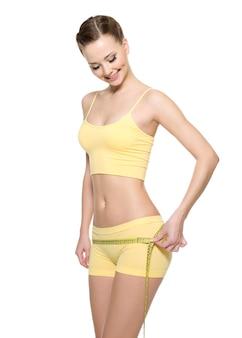 Bella donna felice con il corpo perfetto che misura le natiche con il tipo di misurazione isolato su bianco.