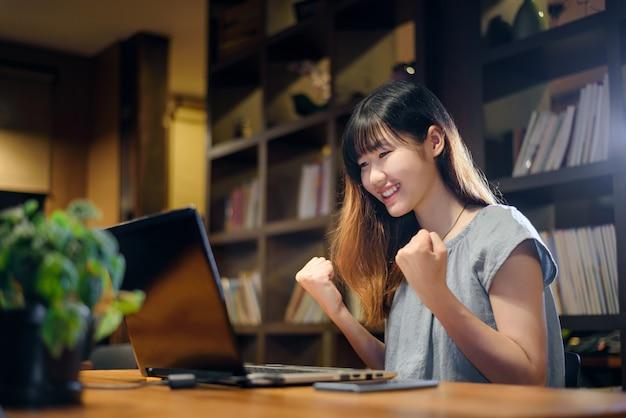 Bella donna felice dell'allievo asiatico che lavora al computer portatile nella biblioteca moderna
