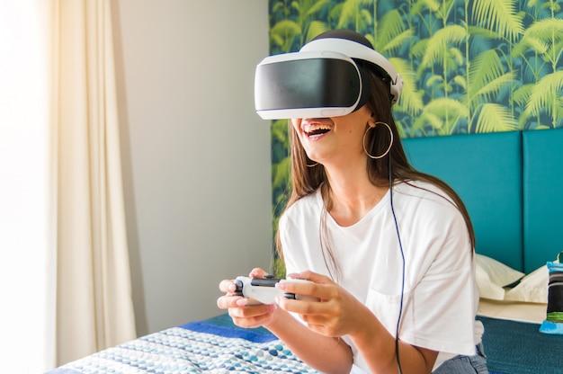 Bella donna felice divertendosi al coperto giocando videogiochi su cuffie da realtà virtuale