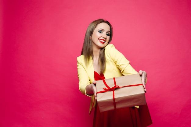 Bella donna felice in occhiali alla moda cat-eye in abito luminoso tenendo regalo di natale.