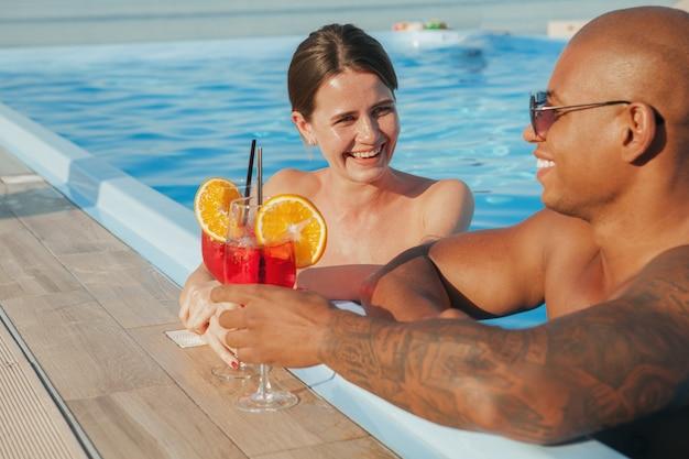 Bella donna felice ridendo, parlando con il suo ragazzo sorseggiando un drink in piscina. amorevole coppia multirazziale che celebra le vacanze estive, bevendo cocktail in spiaggia