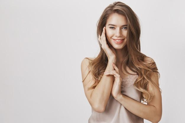 Bella donna femminile sorridente, toccando il viso