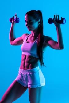 Bella donna fitness lavorando con manubri su sfondo blu chiaro