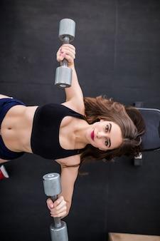 Bella donna forte in forma sportiva che risolve con due manubri