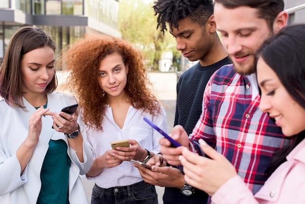 Bella donna guardando fotocamera in piedi tra i suoi amici utilizzando i telefoni cellulari