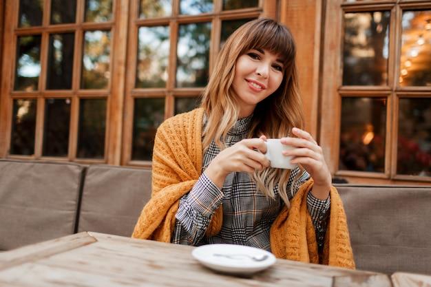 Bella donna ha una pausa caffè in un accogliente bar con interni in legno, parlando al telefono cellulare. tenendo la tazza di cappuccino caldo. stagione invernale. indossare abiti eleganti e plaid giallo.