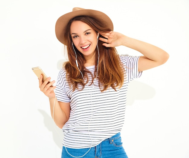 Bella donna in abiti estivi casual hipster senza trucco nella musica d'ascolto del cappello marrone nel telefono con le cuffie isolate su bianco