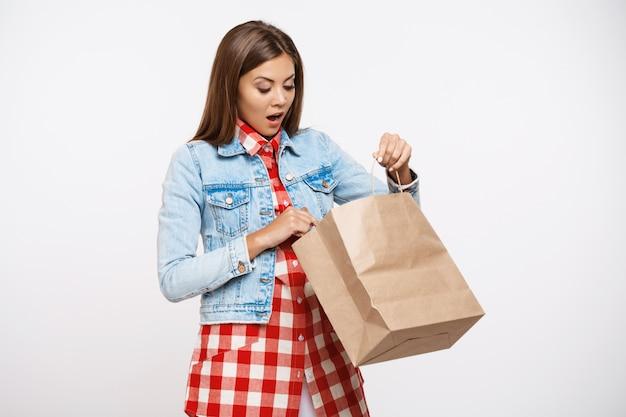 Bella donna in abito a quadri e borsa apribile in giacca di jeans