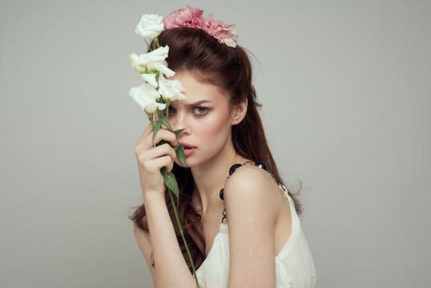 Bella donna in abito bianco e bouquet di fiori decorazione cosmetici lifestyle. foto di alta qualità