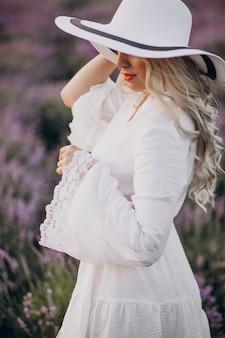 Bella donna in abito bianco in un campo di lavanda