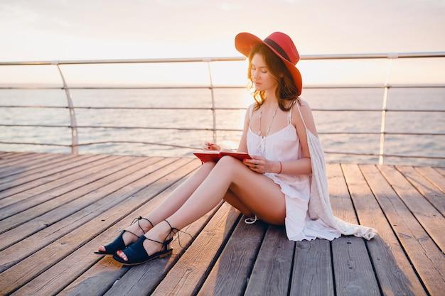 Bella donna in abito bianco seduto in riva al mare all'alba pensando e prendendo appunti nel libro del diario