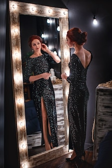 Bella donna in abito da sera nero lucido si trova accanto allo specchio alto scuro