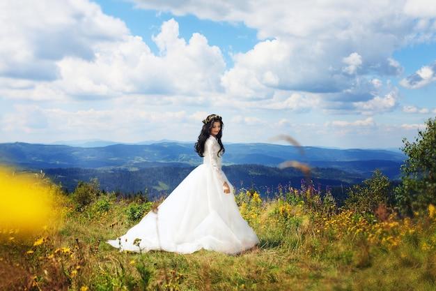 Bella donna in abito da sposa in posa in montagna. servizio fotografico pre-matrimonio