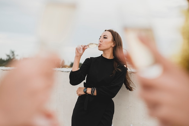 Bella donna in abito nero, bere champagne sullo sfondo di bicchieri di champagne offuscata