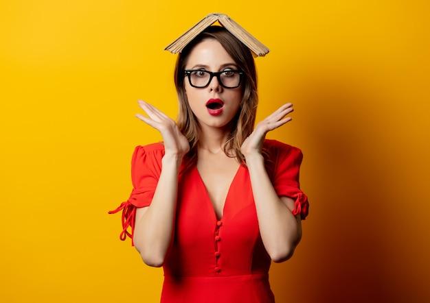 Bella donna in abito rosso con libro sulla parete gialla