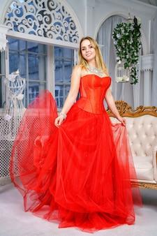 Bella donna in abito rosso in posa sulla fotocamera, affascinante bionda