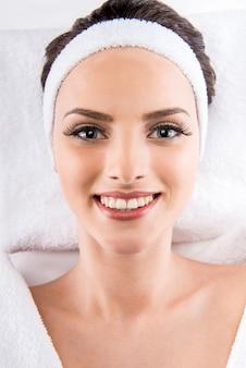 Bella donna in accappatoio bianco rilassante al salone spa.