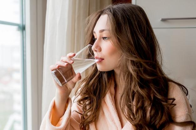 Bella donna in accappatoio che beve acqua fresca a casa