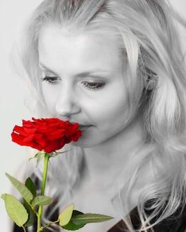 Bella donna in bianco e nero che odora una rosa rossa