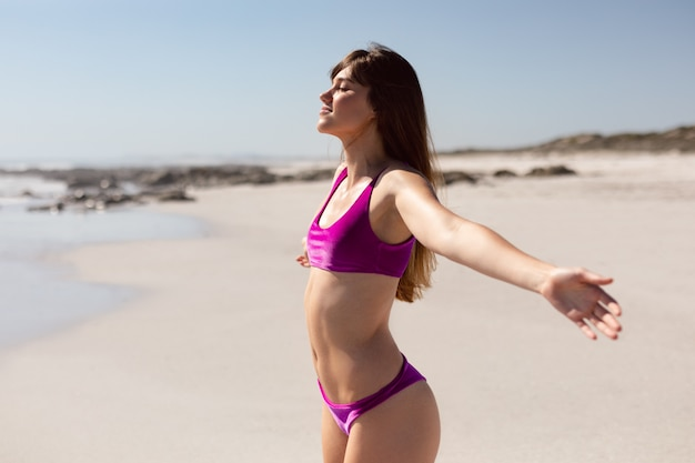 Bella donna in bikini con le braccia distese in piedi sulla spiaggia sotto il sole