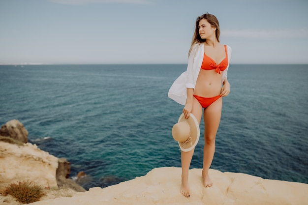Bella donna in bikini e cappello di paglia si sta rilassando sul bordo di una montagna