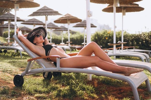 Bella donna in bikini sdraiato sul letto della piscina