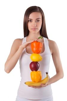 Bella donna in buona salute e giovane che tiene frutta e verdura fresca nelle sue mani. bella ragazza che conduce uno stile di vita sano. ragazza carina vegetariana su.