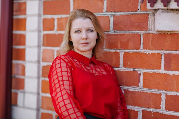 Bella donna in camicia rossa. rughe sul viso della donna. bionda in una camicetta rossa. una bella mamma