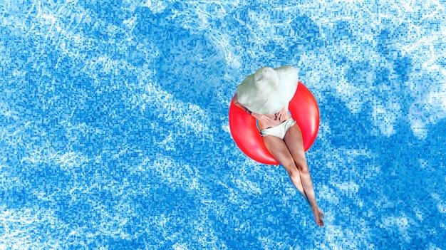 Bella donna in cappello in piscina vista aerea dall'alto dall'alto, giovane ragazza in bikini si rilassa e nuota sulla ciambella anello gonfiabile e si diverte in acqua, località di villeggiatura tropicale