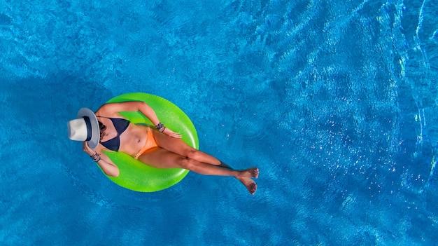 Bella donna in cappello in piscina vista aerea dall'alto, giovane ragazza in bikini si rilassa e nuota sulla ciambella anello gonfiabile e si diverte in acqua in vacanza