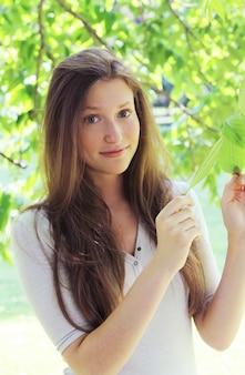 Bella donna in foglie di un albero
