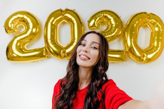Bella donna in maglione rosso che fa selfie divertente davanti ai palloni del nuovo anno 2020
