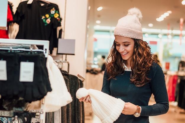 Bella donna in negozio comprando il cappello.