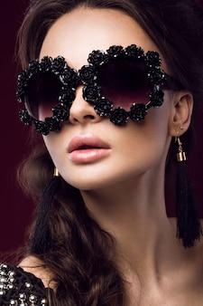 Bella donna in occhiali da sole scuri, con riccioli e trucco da sera