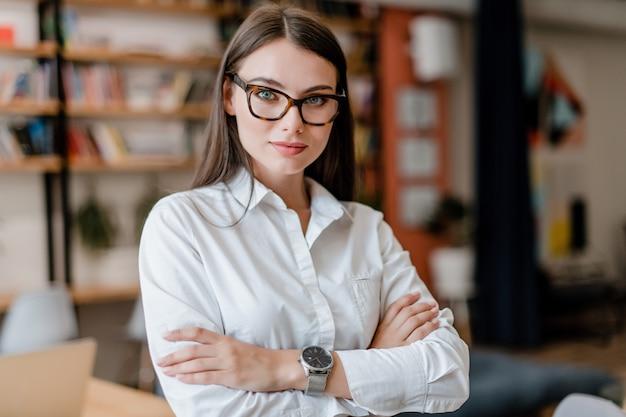 Bella donna in occhiali e camicia in ufficio