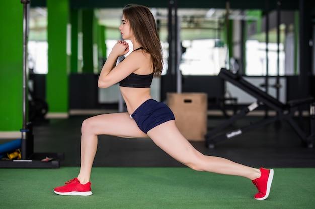 Bella donna in palestra sta facendo diversi esercizi per rendere il suo corpo più forte
