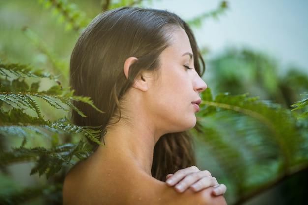 Bella donna in piedi all'aperto contro le piante verdi