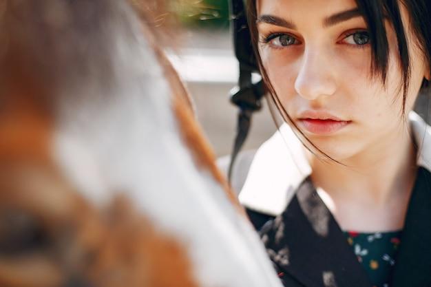 Bella donna in piedi con un cavallo