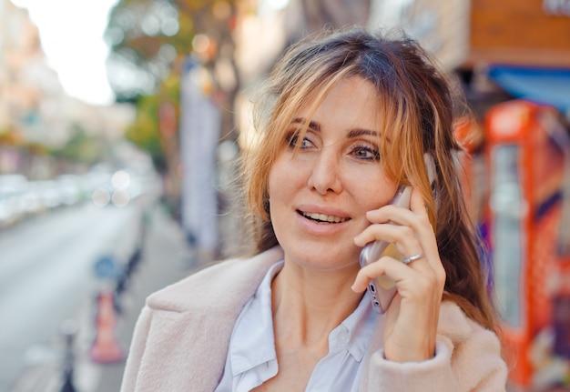 Bella donna in piedi e parlando al telefono in strada durante il giorno e guardando eccitato.