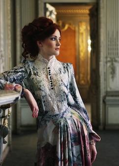 Bella donna in piedi nella stanza del palazzo.