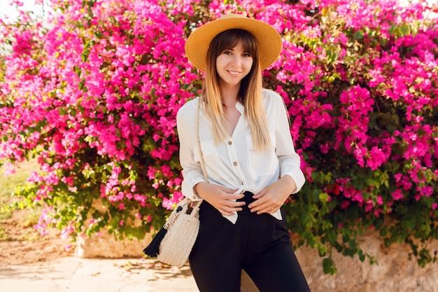 Bella donna in piedi sui fiori rosa indossando cappello di paglia e abbigliamento casual.