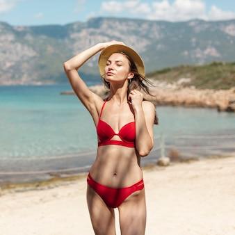 Bella donna in piedi sulla spiaggia