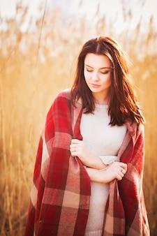 Bella donna in plaid su un campo